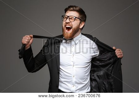 Portrait of a crazy young businessman dressed in suit trying to undress isolated over gray background