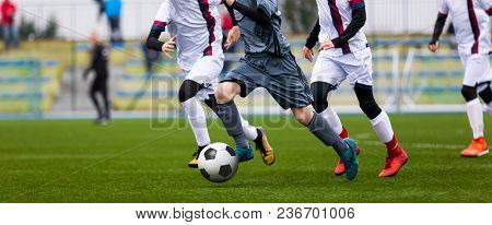Junior Football Match. Soccer Game For Youth Players. Boys Playing Soccer Match On Football Pitch. F