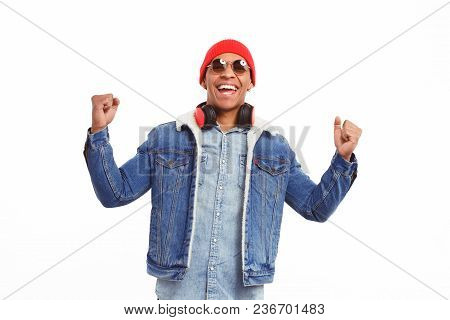 Cheerful Black Man In Stylish Outfit And Headphones With Sunglasses Holding Fists Up Happy With Vict