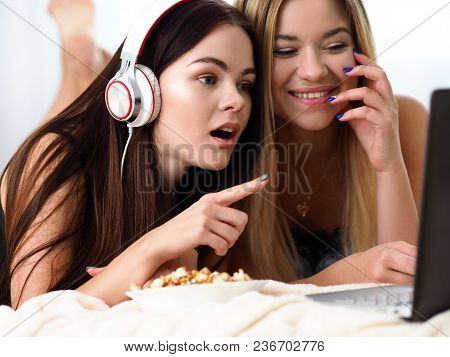 Two Happy Smiling Girlfriends Eat Popcorn In Bed Watching Tv Show Early Morning Holding Remote Contr