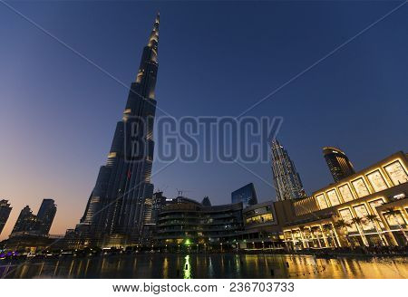 The Impressive Burj Khalifa At Night With A Lights And Reflection In Water