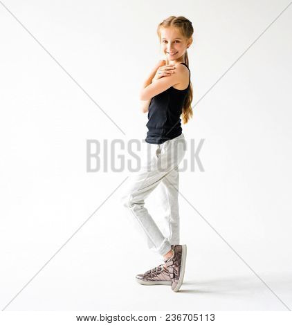 Happy little girl smiling standing in front of camera on white background