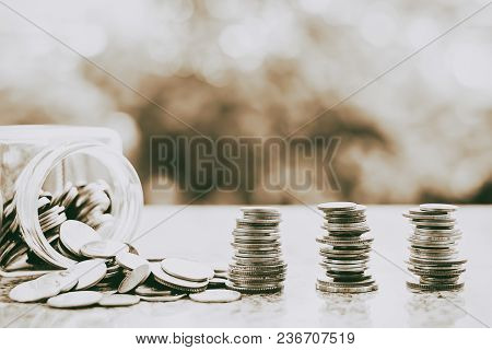 Coins In And Outside The Glass Jar On Blurred Natural Green Background For Investment, Business And