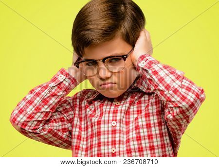 Handsome toddler child with green eyes covering ears ignoring annoying loud noise, plugs ears to avoid hearing sound. Noisy music is a problem. over yellow background