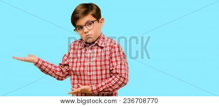 Handsome toddler child with green eyes doubt expression, confuse and wonder concept, uncertain future over blue background