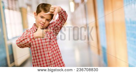 Handsome toddler child with green eyes confident and happy showing hands to camera, composing and framing gesture at school corridor
