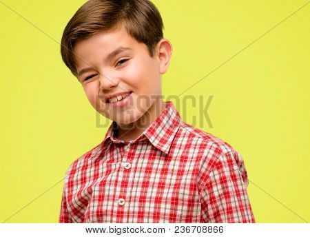 Handsome toddler child with green eyes blinking eyes with happy gesture over yellow background