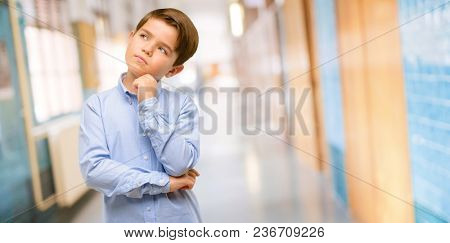 Handsome toddler child with green eyes thinking and looking up expressing doubt and wonder at school corridor