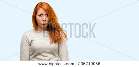 Beautiful young redhead woman with sad and upset expression, unhappy isolated over blue background