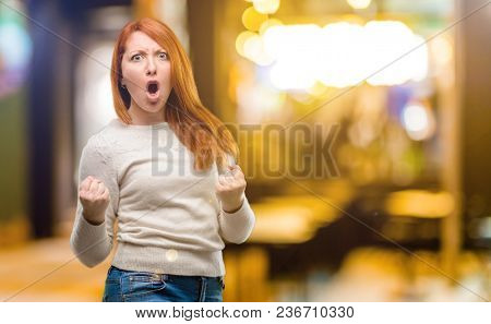 Beautiful young redhead woman happy and excited celebrating victory expressing big success, power, energy and positive emotions. Celebrates new job joyful at night