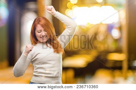 Beautiful young redhead woman happy and excited expressing winning gesture. Successful and celebrating victory, triumphant at night