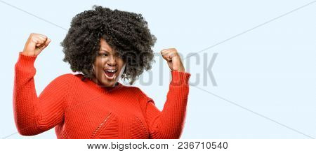 Beautiful african woman happy and excited celebrating victory expressing big success, power, energy and positive emotions. Celebrates new job joyful, blue background