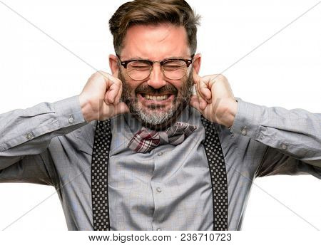 Middle age man, with beard and bow tie covering ears ignoring annoying loud noise, plugs ears to avoid hearing sound. Noisy music is a problem. isolated over white background