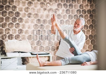 Senior Physiotherapist Working With An Unrecognizable Female Patient.