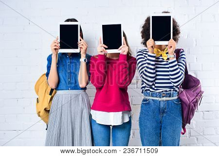 Obscured View Of Students Showing Tablets With Blank Screens In Hands Against White Brick Wall