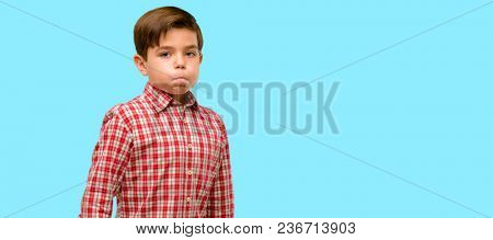 Handsome toddler child with green eyes puffing out cheeks, having fun making funny face over blue background