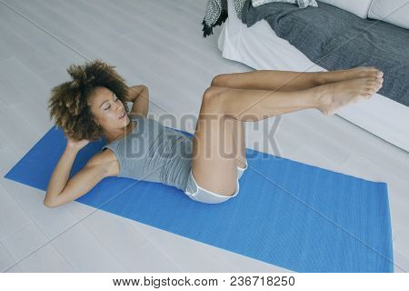 Beautiful young model in shorts lying on mat at home holding hands behind head and training abdominal muscles breathing with concentration.
