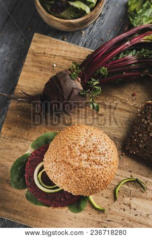high angle view of a beet burger sandwich on a wooden chopping board placed on a rustic wooden table, next to a sliced beet