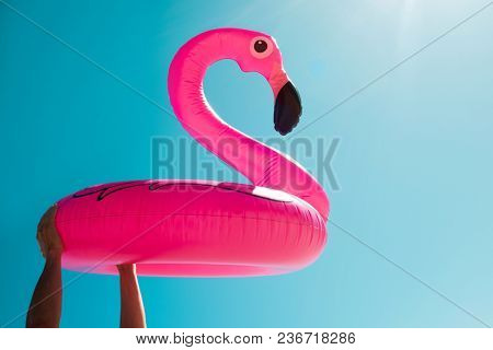 closeup of a young caucasian man on the beach with a swim ring in the shape of a pink flamingo in his hands against the blue sky, with some blank space around it