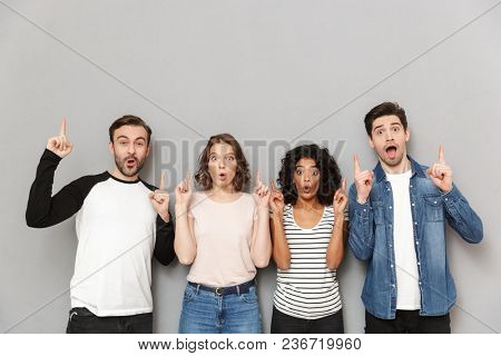 Image of shocked excited group of friends standing isolated over grey wall background looking camera pointing.