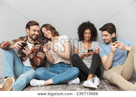 Photo of happy group of friends sitting isolated over grey wall background using mobile phone chatting.
