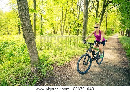 Woman Cycling A Mountain Bike In A City Park, Summer Day. Inspire And Motivate Concept For Outdoors