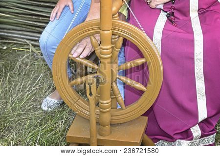 The Woman In The National Dress Shows An Old Wooden Spinning Wheel.