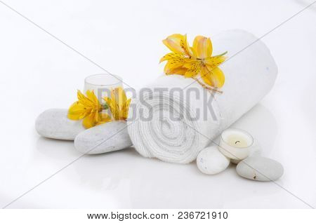 Spa setting on mat with many salt,pink orchid on towel,candle