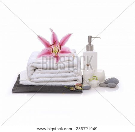 Spa setting on mat background with lily, towel,candle,bottle, oil,salt in bowl, stones