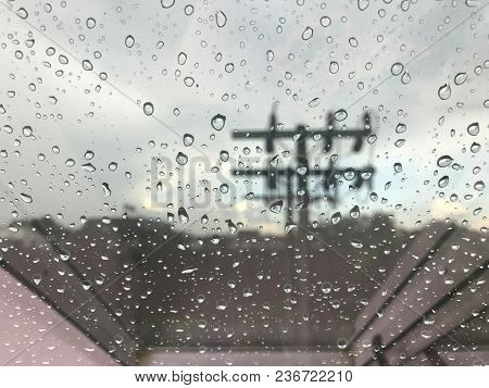 Close Up View Of Rain Drop On Office Or House Window During Raining With Electric Pole And City Back