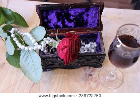 Pictured In The Photo A Red Rose Lies On The Jewelry Box.