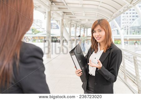 Young Asian Businesswoman Holdind File And Looking At Colleague  - Business Concept.