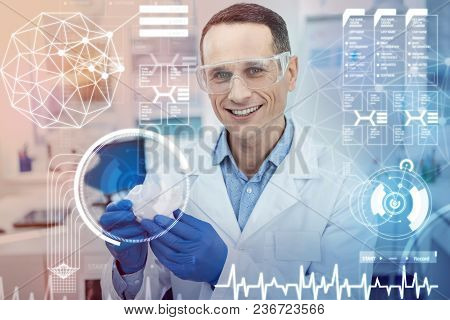 Innovation. Clever Experienced Young Doctor Smiling And Feeling Proud While Using Modern Technologie