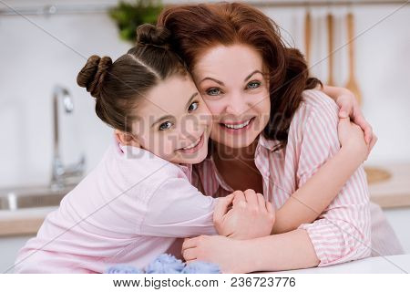 Close-up Portrait Of Embracing Grandmother And Little Granddaughter Looking At Camera