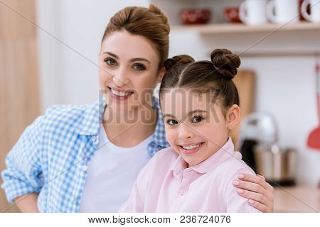 Close-up Portrait Of Young Happy Mother And Daughter Looking At Camera