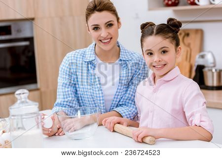 Mother And Daughter Cooking Together At Kitchen And Looking At Camera