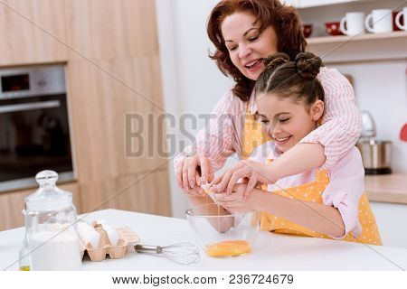 Grandmother With Little Granddaughter Preparing Dough For Cooking At Kitchen