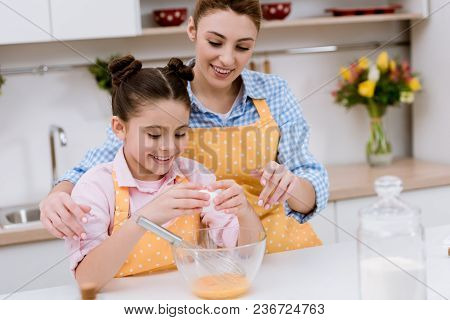 Mother And Daughter Cooking Together At Kitchen