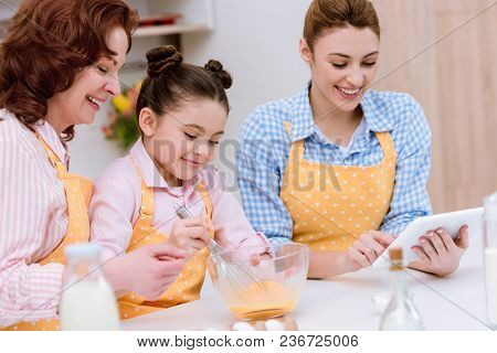 Three Generations Of Happy Women In Aprons Preparing Dough Together At Kitchen
