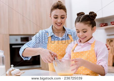 Mother And Daughter Mixing Dough For Pastry Together