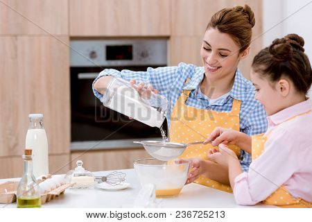 Mother And Daughter With Sieve Preparing Dough For Pastry Together