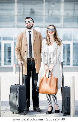 Business Couple In Coats Standing Near The Airport With Luggage During The Business Trip