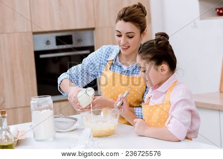 Beautiful Young Mother And Daughter Pouring Milk Into Bowl For Dough At Kitchen