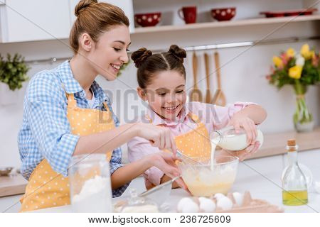 Beautiful Young Mother And Daughter Pouring Milk Into Bowl For Dough