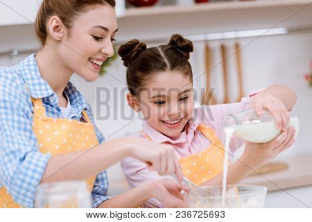 Happy Mother And Daughter Pouring Milk Into Bowl For Dough