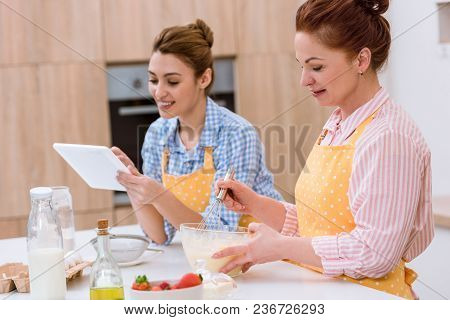 Young Woman And Her Mother Cooking Together At Kitchen And Using Tablet