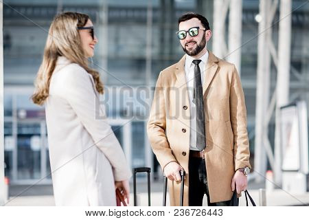 Business Couple In Coats Talking Near The Airport With Luggage During The Business Trip