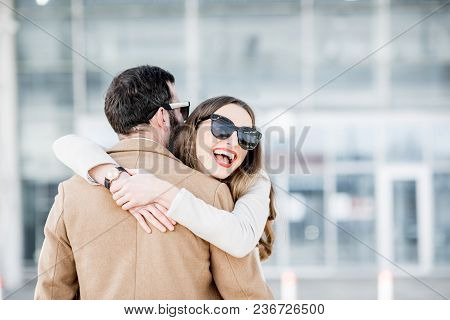 Young Couple Hugging Together During The Meeting After The Long Business Travel Near The Airport