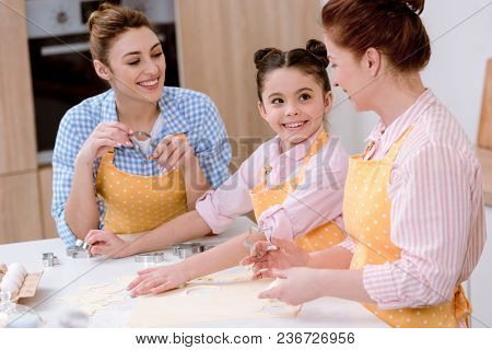 Three Generations Of Beautiful Women Cooking Together At Kitchen