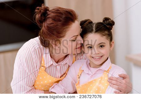 Grandmother Embracing Little Granddaughter While Cooking In Aprons
